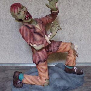 Zombie en mauvaise posture, un genoux au sol, il essaie d'éviter les coups.