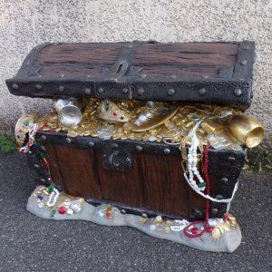 Coffre débordant de pièces d'or, de bijoux et autres objets précieux.